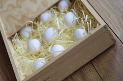 Eggs on a soft substrate in a wooden box. White eggs on a soft substrate in a wooden box. Unusual perspective Stock Image
