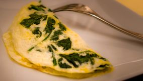 Egg and spinach omelet. Eggs and spinach omelet with fork royalty free stock images