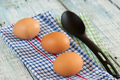 Eggs with spoon and dish towel Stock Photos