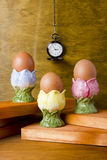 Eggs in the stands and pocket watches Royalty Free Stock Photos