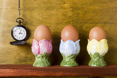 Eggs in the stands and pocket watches Stock Photography