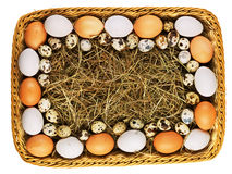 Eggs and straw in basket Royalty Free Stock Photos