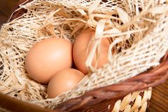 Eggs in the straw and basket Stock Images