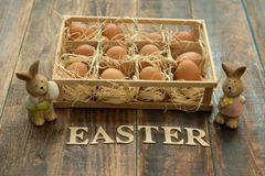 Eggs on straw placed with two funny rabbit to easter decoration Royalty Free Stock Photos