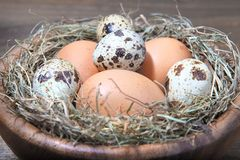 Eggs and straw in a wooden bowl Stock Photo