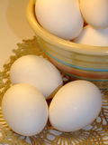 Eggs and Striped Bowl - Close-up. Eggs, bowl and crocheted doily on table Royalty Free Stock Image