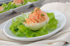 Eggs stuffed with salmon pate. Eggs stuffed with pate salmon with red pepper in lettuce leaves Stock Photo