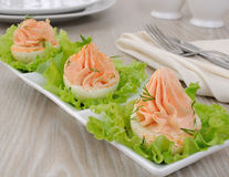 Eggs stuffed with salmon pate. Eggs stuffed with pate salmon with red pepper in lettuce leaves Royalty Free Stock Images