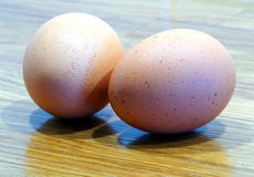 Eggs on a table. Two brown eggs on an oak table Royalty Free Stock Image