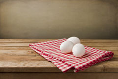 Eggs on tablecloth. Over wooden background Royalty Free Stock Images