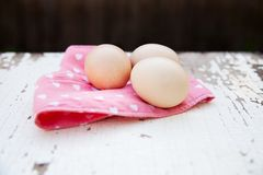 Eggs on tablecloth over wooden background Stock Photo