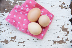 Eggs on tablecloth over wooden background Stock Image