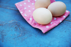 Eggs on tablecloth over wooden background Stock Photography