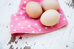 Eggs on tablecloth over wooden background Stock Images