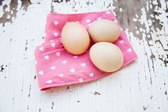 Eggs on tablecloth over wooden background Royalty Free Stock Photos