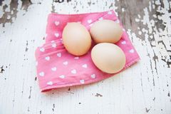 Eggs on tablecloth over wooden background Royalty Free Stock Photo