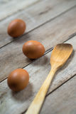 Eggs. Three eggs and a wooden spoon Royalty Free Stock Photography