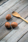 Eggs. Three eggs and a wooden spoon Royalty Free Stock Photo