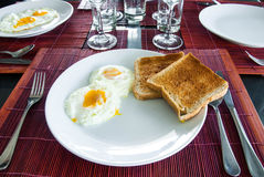 Eggs and toasts on white plate on dining table Stock Images