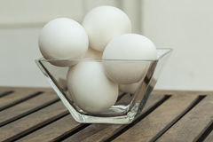 Eggs in a transparent glass bowl isoated on wooden table. Front View. Eggs in a transparent glass bowl isoated on wooden table Stock Photo