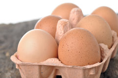Eggs in a tray on a wooden table. Royalty Free Stock Images