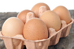 Eggs in a tray on a wooden table. Royalty Free Stock Image