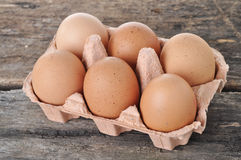 Eggs in a tray on a wooden table. Royalty Free Stock Photo