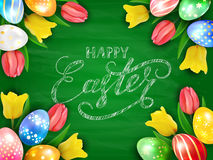 Eggs with tulips and Happy Easter on green chalkboard background. Colorful Easter eggs with tulips on green chalkboard background, lettering Happy Easter writing Stock Images