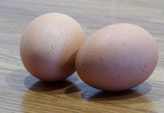 Eggs. Two brown eggs on an oak counter top Royalty Free Stock Image