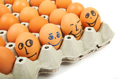 Eggs with various emotions in a cardboard box on a white backgro Royalty Free Stock Images