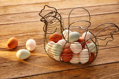 Eggs in a vintage hen shape basket on wood royalty free stock photos