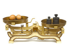 Eggs on weight. Two eggs on ancient weight. Horizontal position Royalty Free Stock Photo