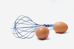 Eggs and whisk. An eggs in front of kitchen whisk Royalty Free Stock Image