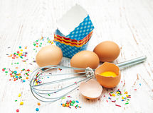 Eggs, whisk and cupcake liners Royalty Free Stock Photo