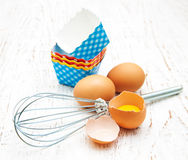 Eggs, whisk and cupcake liners Stock Photography
