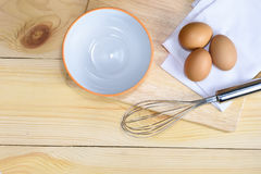 Eggs with whisk and empty orange bowl Stock Photos