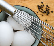 Eggs Whisk and Peppercorns. Thee eggs in a bowl, steel balloon whish and black peppercorns on butcher block counter top royalty free stock photography