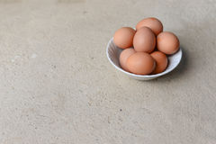 Eggs in white bowl on cement floor Royalty Free Stock Photography