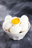 Eggs in a white bowl, egg yolk in a shell Stock Photos
