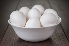 Eggs in white bowl on wooden table. Some eggs in white bowl on wooden table stock photo