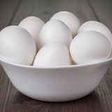 Eggs in white bowl on wooden table Royalty Free Stock Image