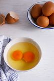 Eggs in white cup prepare for cooking. Egg yorks with egg shell in a small cup prepare for cooking put on wooden table Stock Photography