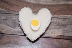Eggs and white rice. With wooden background, Heart shape Stock Photos