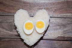 Eggs and white rice. With wooden background, Heart shape Stock Images