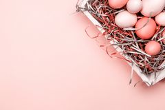 Eggs in a white tray. Creative Easter concept. Modern solid pink background. . Living coral theme - color of the year 2019. Eggs in a white tray. Creative Easter stock image