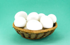 Eggs in wicker basket. Against green background Stock Photos