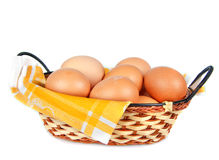 Eggs in wicker basket. With yellow serviette on white background Stock Image