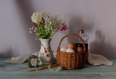 Eggs in a wicker basket, a bouquet of tulips, icon and church candles. The easter still life. Eggs in a wicker basket, a bouquet of tulips, icon and church Royalty Free Stock Photos