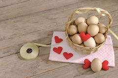 Eggs in a wicker basket with heart-shaped on wooden table Royalty Free Stock Images