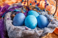 Eggs in a wicker basket are painted in an unusual blue color. Royalty Free Stock Images